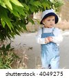 Cute small boy under tree looking forward - stock photo