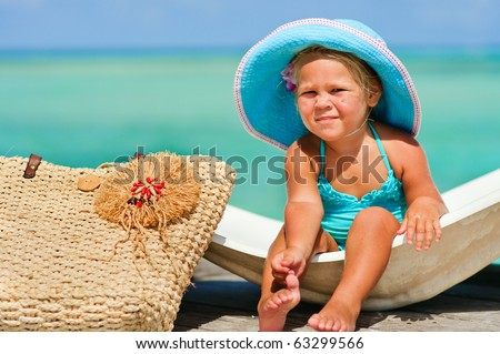 cute small girl in big hat and bikini relax at turquoise ocean background - stock photo
