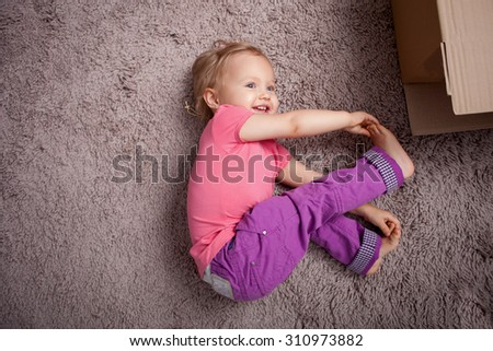 Cute small girl is relaxing on flooring with joy. She is lying on carpet near boxes. The kid is touching her thumbs with her arms and smiling. Copy space in left side - stock photo