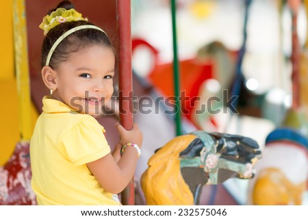 Cute small mixed race girl riding a colorful carousel - stock photo