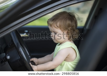 Cute small serious baby boy driver sitting in big car with black salon holding wheel learning to drive in summer, horizontal picture - stock photo