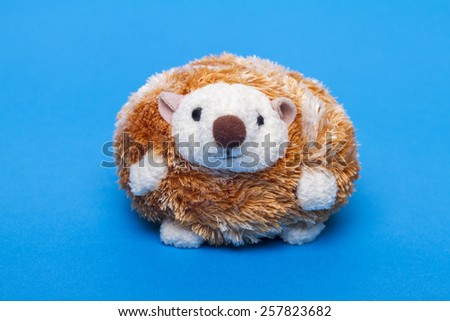 Cute small stuffed hedgehog toy over a blue background. - stock photo