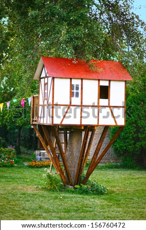 Cute small tree house for kids on backyard. German style. - stock photo