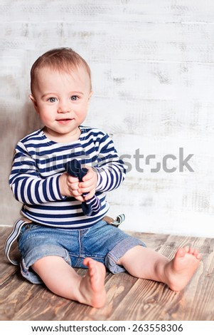 Cute smiling  baby in stripped vest with bare foot and socks in his hands - stock photo