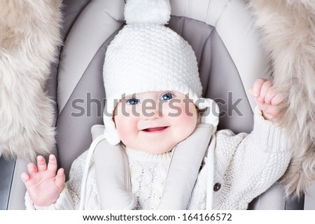 Cute smiling baby sitting in a stroller on a cold winter day - stock photo