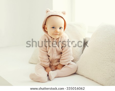Cute smiling baby sitting in white room at home  - stock photo