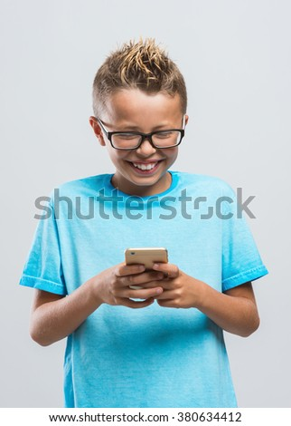 Cute smiling blonde boy playing with his touch screen smart phone - stock photo