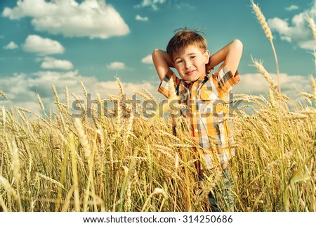 Cute smiling boy enjoyes summer day in the wheat field. Summer holidays.  - stock photo