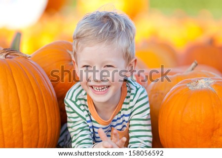 cute smiling boy having fun at the pumpkin patch - stock photo