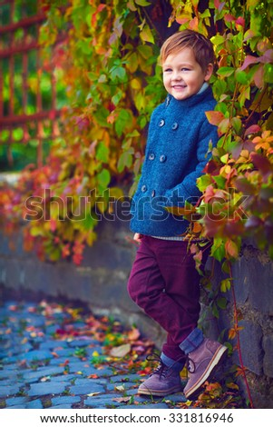 cute smiling boy posing near the colorful wall