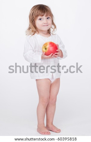 Cute smiling child standing with apple at hands
