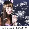 Cute smiling female blowing lots of soap bubbles during a birthday party celebration - stock photo