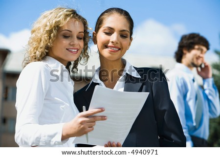 Cute smiling female students reading the documents outside and handsome young man talking by the phone on the background - stock photo