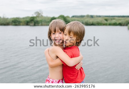 Cute smiling fraternal twins enjoying their time at the beach. Brother and sister hugging. Friends having fun during summer vacation. Nice hot day at the lake. - stock photo