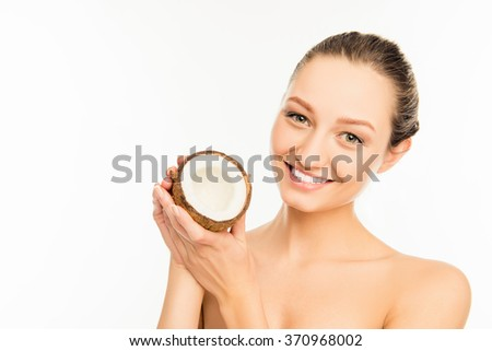 Cute smiling girl holding half of coconut in hands - stock photo