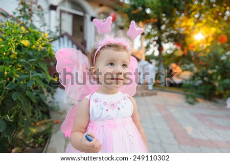 cute smiling girl in butterfly dress - stock photo