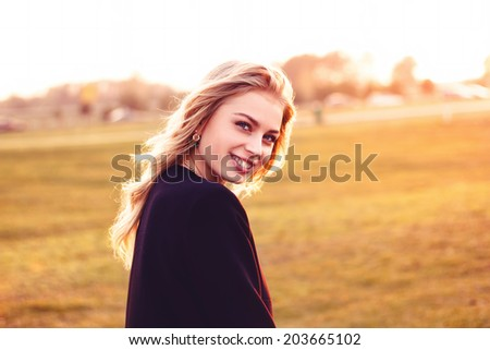 Cute smiling girl looking at you on a sunny day - stock photo