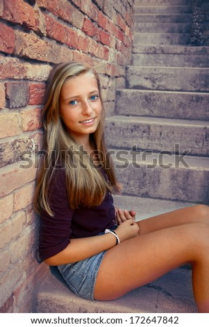 Cute, smiling girl sitting on brick steps, close up - stock photo