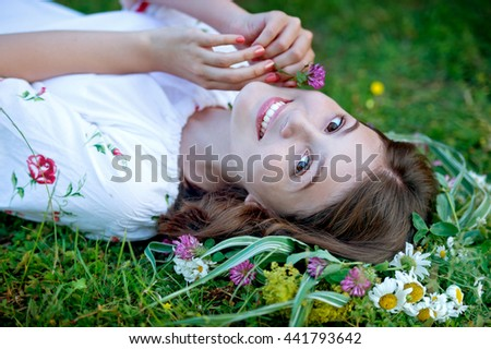Cute smiling girl with flower wreath on the meadow at the farm. Portrait girl outdoors. Midsummer. Earth Day - stock photo