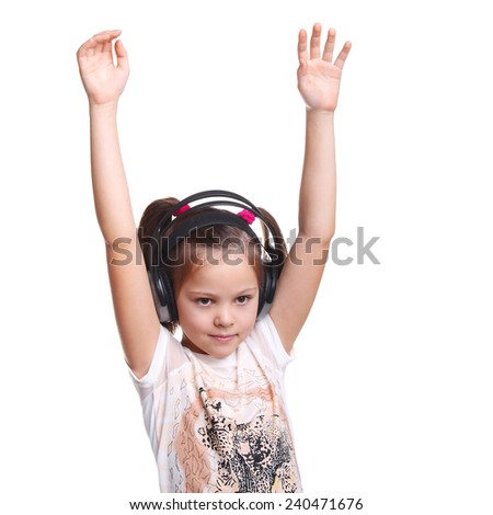 cute smiling happy little child in the headphones with her hands up - stock photo