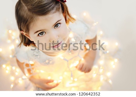 Cute, smiling, happy three years old girl sitting with glowing Christmas lights - stock photo