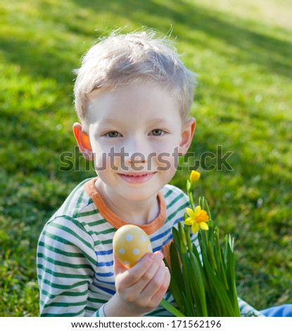 cute smiling little boy holding bright yellow easter egg and blooming daffodils at spring time