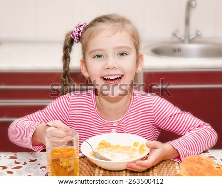 Cute smiling little girl having breakfast cereals with milk and juice in the kitchen - stock photo