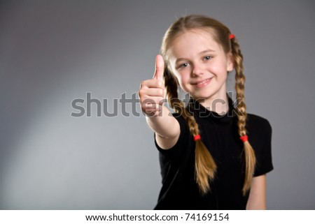 Cute smiling little girl holding thumbs up - stock photo