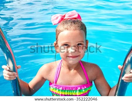 Cute smiling little girl in swimming pool on summer vacation   - stock photo
