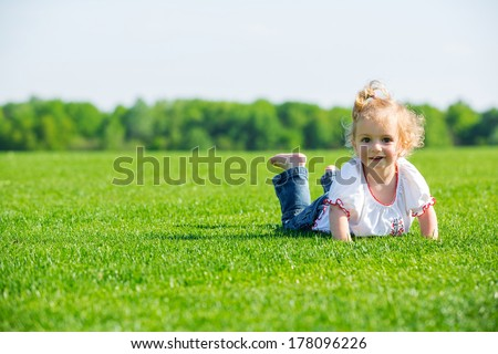 Cute smiling little girl lying on a fresh green grass in a field, looking into the camera - stock photo