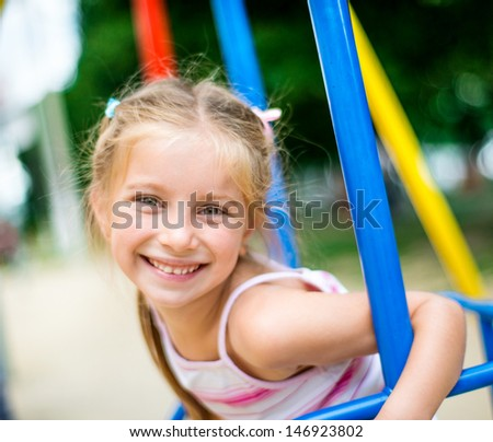 cute smiling little girl on a swing - stock photo