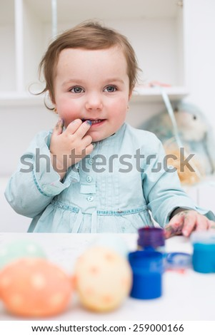 Cute smiling little girl painting colorful easter eggs