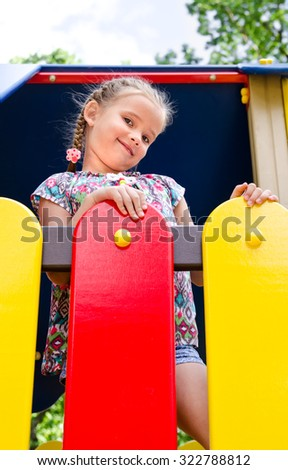 Cute smiling little girl playing on playground equipment