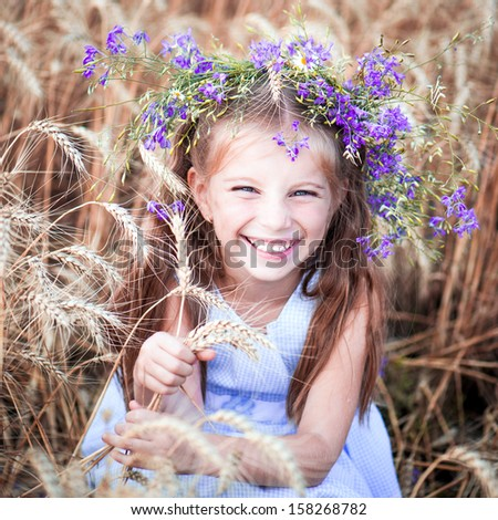 cute smiling little girl with a wreath on his head in a field of wheat close-up - stock photo