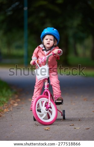 Cute smiling little girl with bicycle and helmet on road in the park