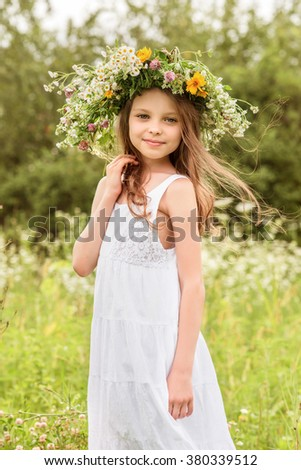 Cute smiling little girl with flower wreath on the meadow at the farm. Portrait of adorable small kid outdoors. Midsummer. - stock photo