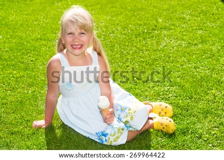 Cute smiling little girl with ice cream on the grass