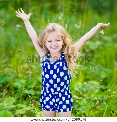 Cute smiling little girl with long blond curly hair and flower in her hands. Girl with raised hands. Outdoor full-length portrait in summer park on bright sunny day. Child in green grass field. - stock photo