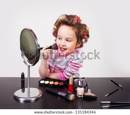 cute smiling little girl with makeup brush - stock photo