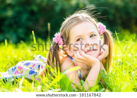 Cute smiling little girl with two blonde ponytails laying on grass in summer park, outdoor portrait.