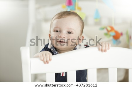 Cute smiling 9 month old baby standing in white wooden crib - stock photo