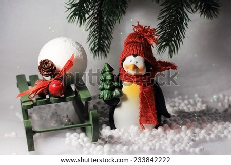 Cute smiling penguin with red scarf and hat, holding a Christmas tree in its hand, standing in the snow.Beautiful composition for winter background.