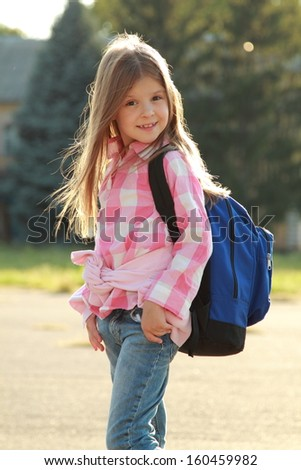 Cute smiling schoolgirl in casual clothes with a backpack goes to school outdoors on Education - stock photo