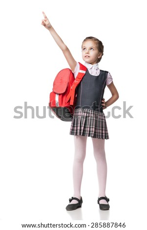Cute smiling schoolgirl in uniform standing on white background and pointing up - stock photo