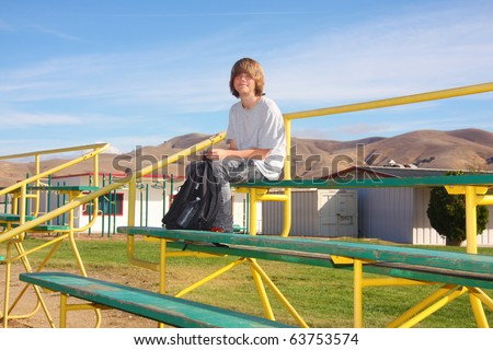 Cute smiling teen boy sitting a the top of school bleachers. - stock photo