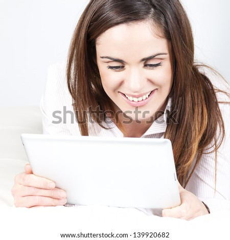 Cute smiling woman on sofa with tablet - stock photo