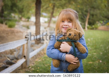 Cute Smiling Young Girl Hugging Her Teddy Bear on Bench Outside. - stock photo