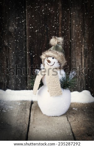 Cute snowman, gift box and Christmas decorations on vintage wooden background - stock photo