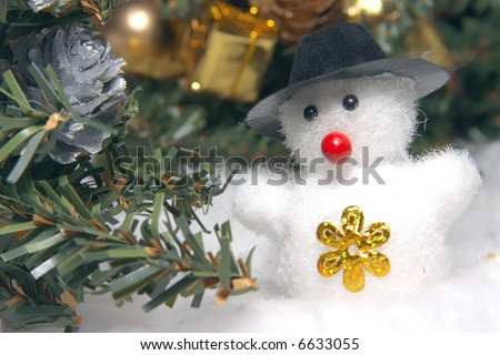 cute snowman to a dark hat in an environment of snowdrifts and christmas evergreen trees - stock photo