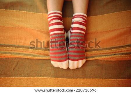 cute socks on the bedspread. - stock photo